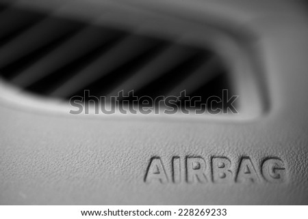"The word ""Airbag"" is written inside a car."