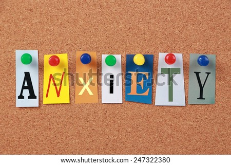 The word Anxiety in cut out magazine letters pinned to a cork board. - stock photo