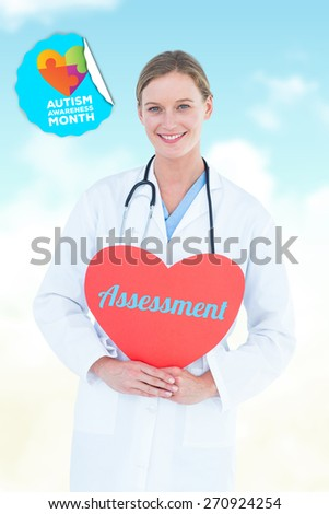 The word assessment and doctor holding red heart card against blue sky - stock photo