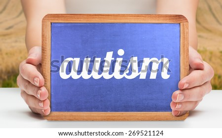 The word autism and hands showing chalkboard against rural fields - stock photo