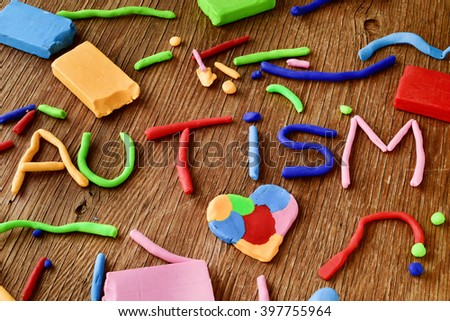 the word autism made from modelling clay of different colors on a rustic wooden surface - stock photo