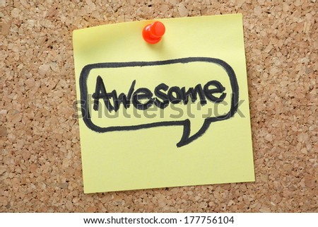 The word Awesome in a speech bubble written by hand in felt tip on a yellow sticky note and pinned to a cork notice board - stock photo