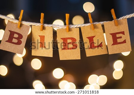 The word BIBLE printed on clothespin clipped cards in front of defocused glowing lights. - stock photo