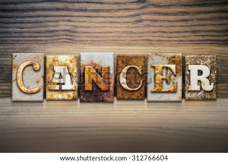 """The word """"CANCER"""" written in rusty metal letterpress type sitting on a wooden ledge background. - stock photo"""