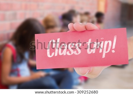 The word class trip! and hand showing card against cute pupils using mobile phone - stock photo