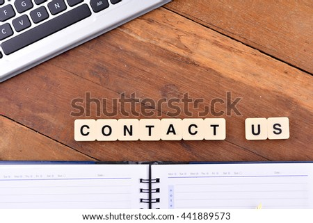 The word contact us written in tiles on a wooden surface with blank notebook and keyboard