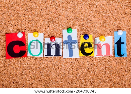 The word content in cut out magazine letters pinned to a cork notice board
