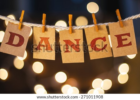 The word DANCE printed on clothespin clipped cards in front of defocused glowing lights. - stock photo