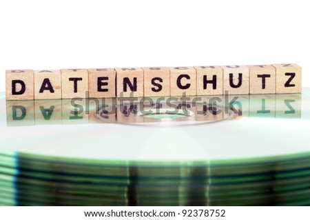 The word Datenschutz (data protection) written in wooden letters standing on a computer-CD - stock photo