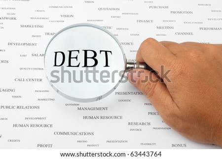 The word DEBT is magnified. - stock photo