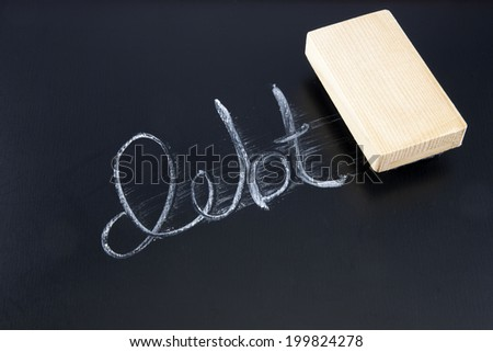 The word DEBT written in chalk on a chalkboard being rubbed out by an eraser - stock photo
