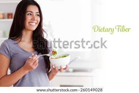 The word dietary fiber against attractive woman enjoying a bowl of salad while standing
