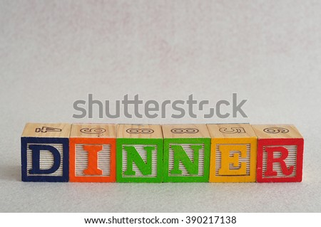 The word dinner spelled with alphabet blocks isolated on a white background - stock photo