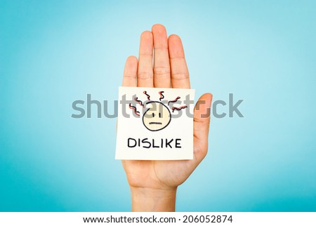 The word dislike and emoticon/emoji stick note on the palm of the hand up, with blue background. Bad feelings, not agree. - stock photo