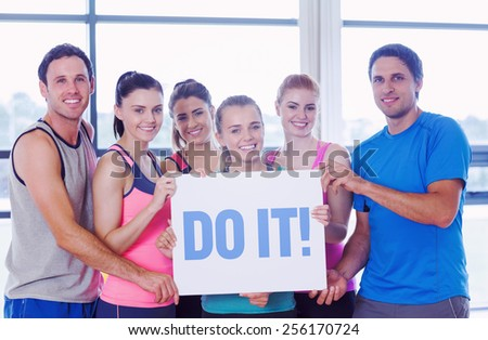 The word do it! against portrait of a group of fitness class holding blank paper - stock photo