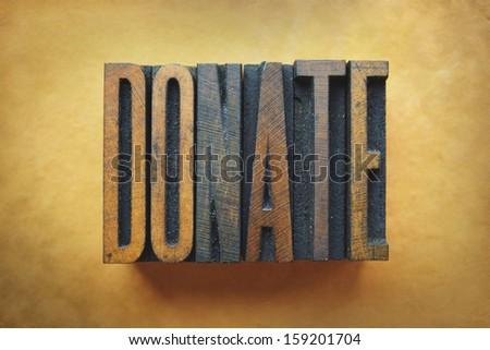 The word DONATE written in vintage letterpress type. - stock photo