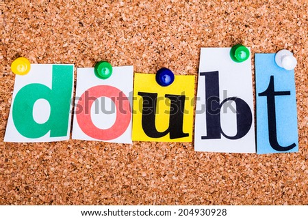 The word doubt in cut out magazine letters pinned to a cork notice board - stock photo