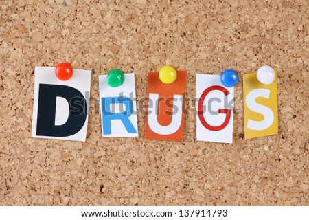 The word Drugs in cut out magazine letters pinned to a cork notice board