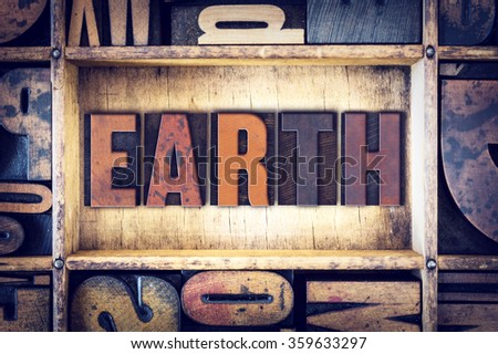 "The word ""Earth"" written in vintage wooden letterpress type."