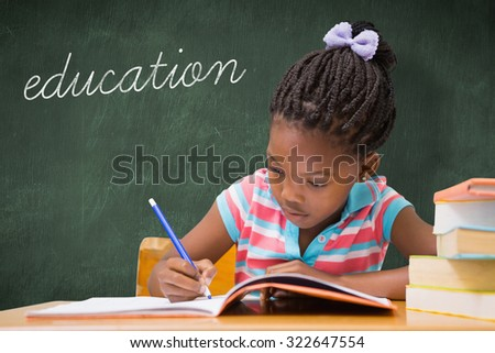 The word education and cute pupils writing at desk in classroom against green chalkboard - stock photo