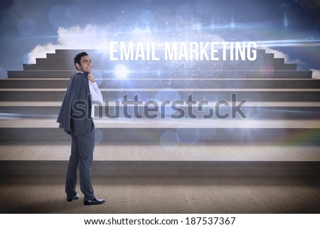 The word email marketing and smiling businessman standing against steps against blue sky