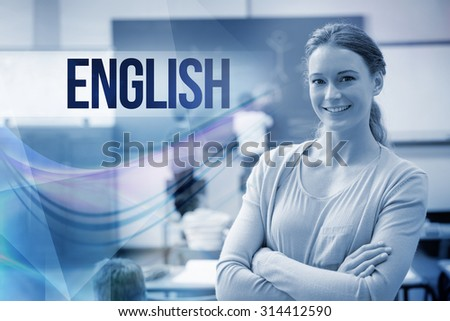 The word english against pretty teacher smiling at camera at back of classroom - stock photo