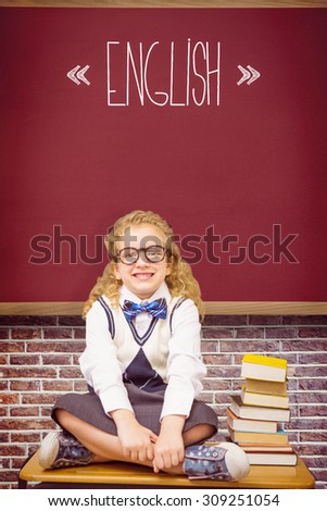 The word english and cute pupil sitting on table against red background - stock photo