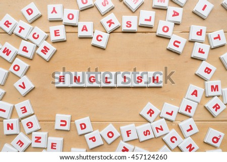 "the word ""English"" spelled using letter tiles on wooden background - stock photo"