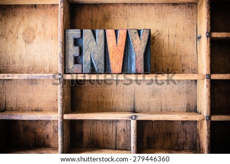 The word ENVY written in vintage wooden letterpress type in a wooden type drawer. - stock photo