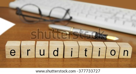 The word erudition on wood stamp stacking on desk with keyboard, vintage retro image style