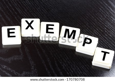 The word exempt spelled out with white tiles on black background - A term used for business in finance and stock market trading - stock photo