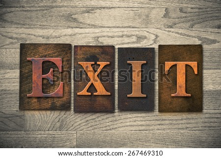 """The word """"EXIT"""" theme written in vintage, ink stained, wooden letterpress type on a wood grained background. - stock photo"""