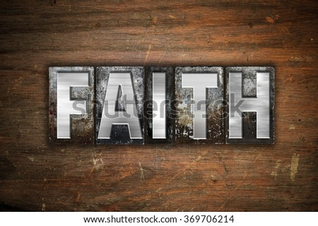 """The word """"Faith"""" written in vintage metal letterpress type on an aged wooden background. - stock photo"""