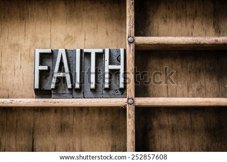"The word ""FAITH"" written in vintage metal letterpress type sitting in a wooden drawer. - stock photo"