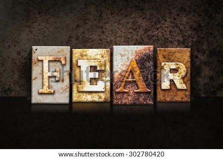"The word ""FEAR"" written in rusty metal letterpress type on a dark textured grunge background. - stock photo"