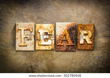 """The word """"FEAR"""" written in rusty metal letterpress type on an old aged leather background. - stock photo"""