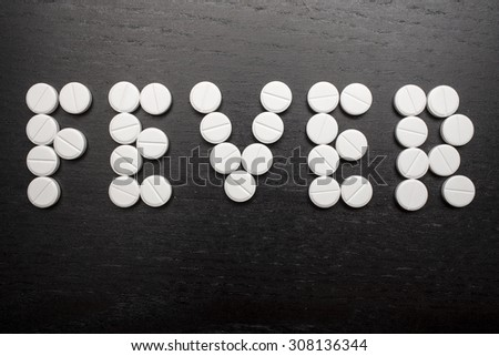 "the word ""fever"" is made on a black table using white medicinal tablets"