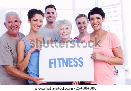 The word fitness against fit people holding blank board in yoga class - stock photo