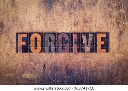"""The word """"Forgive"""" written in dirty vintage letterpress type on a aged wooden background. - stock photo"""