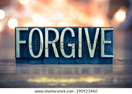 The word FORGIVE written in vintage metal letterpress type on a soft backlit background. - stock photo