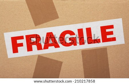 The word Fragile on sticky packaging tape fixed to a cardboard box - stock photo
