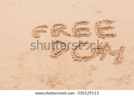 The word 'Freedom' written on the sand on sand.