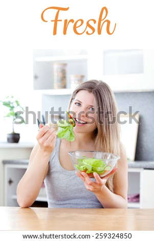 The word fresh against bright woman eating salad in the kitchen