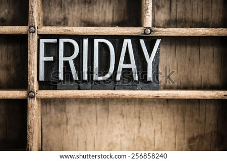 """The word """"FRIDAY"""" written in vintage metal letterpress type in a wooden drawer with dividers. - stock photo"""