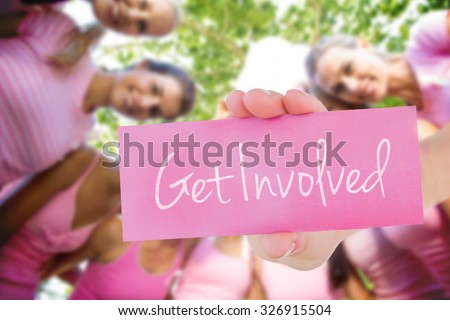 The word get involved and young woman holding blank card against smiling women in pink for breast cancer awareness - stock photo