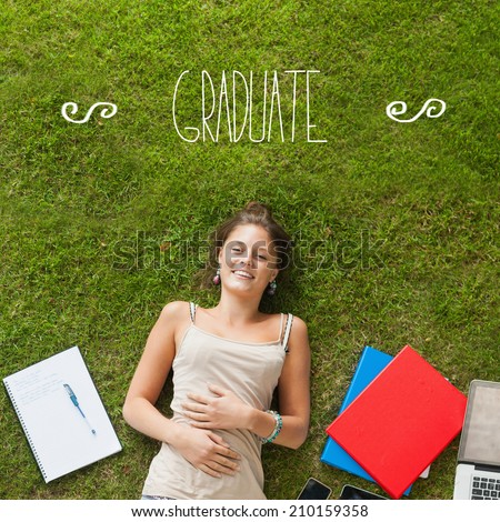 The word graduate against pretty student lying on grass - stock photo