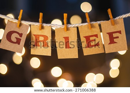 The word GRIEF printed on clothespin clipped cards in front of defocused glowing lights. - stock photo