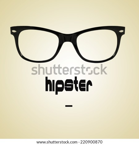 the word hipster and a black plastic rimmed eyeglasses on a beige background with a retro effect - stock photo