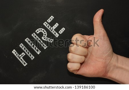 The word Hire in stencil lettering on a blackboard with a hand giving the Thumbs Up sign