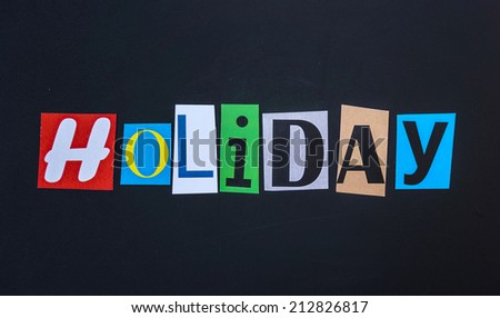 The word holiday in cut out magazine letters on blackboard